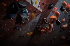 Athletic man practicing in a bouldering gym. Athletic man practising in a bouldering gym stock photo
