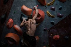 Athletic man practicing in a bouldering gym. Athletic man practising in a bouldering gym stock images