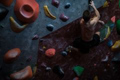 Athletic man practicing in a bouldering gym. Athletic man practising in a bouldering gym stock photography