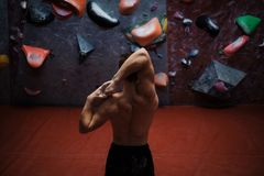 Athletic man stretching before climbing in a bouldering gym. Athletic man practising in a bouldering gym royalty free stock image