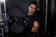 athletic man preparing gym machine for workout Stock Image