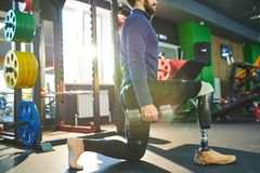 Athletic man with prosthetic leg performing exercise with weight. Serious athletic young man with prosthetic leg standing on one knee and holding dumbbells while royalty free stock photos