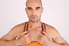 Athletic man pulling his orange tank top. Fit handsome bald Caucasian man Stock Image