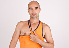 Athletic man pulling his orange tank top. Fit handsome bald Caucasian man Stock Photo