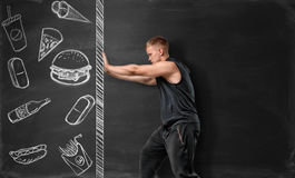 Athletic man pushing the drawn wall with fast food sketches. Stock Photo