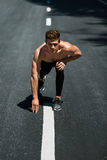 Athletic Man Ready To Start Running Outdoors. Sports Workout Concept. Athletics. Athletic Man With Fit Muscular Body In Starting Position For Running On Road Royalty Free Stock Photography