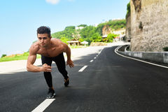 Athletic Man Ready To Start Running Outdoors. Sports Workout Concept. Athletics. Athletic Man With Fit Muscular Body In Starting Position For Running On Road Royalty Free Stock Photo