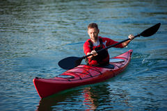 Athletic man in the red kayak races Royalty Free Stock Images