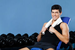 Athletic man rests in gym Royalty Free Stock Image