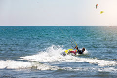 Athletic man riding on kite surf board on a sea waves Stock Image