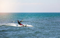 Athletic man riding on kite surf board on a sea waves Stock Images