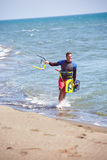 Athletic man riding on kite surf board on a sea waves Stock Photos
