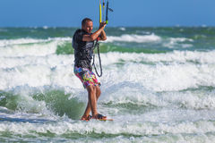 Athletic man riding on kite surf board sea waves Royalty Free Stock Photo