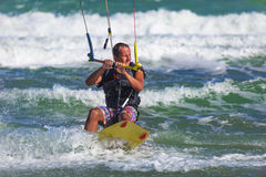 Athletic man riding on kite surf board in sea waves Stock Photography