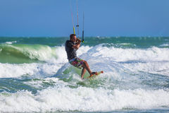 Athletic man riding on kite surf board in sea waves Royalty Free Stock Photos