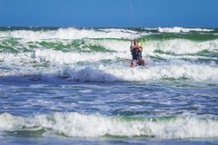 Athletic man riding on kite surf board in sea waves Stock Images