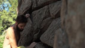 Athletic man rock climber climbs on a cliff, reaching and gripping hold, attaching belay rope.