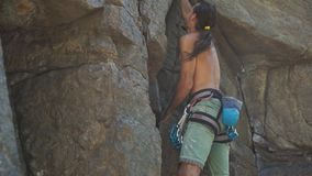 Athletic man rock climber climbs on a cliff, reaching and gripping hold.