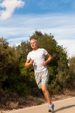 Athletic man runner jogging in nature outdoor Stock Photos