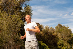 Athletic man runner jogging in nature outdoor Royalty Free Stock Image