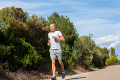Athletic man runner jogging in nature outdoor Royalty Free Stock Images