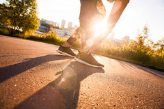 Athletic man runner touching foot in pain due to sprained ankle Royalty Free Stock Images