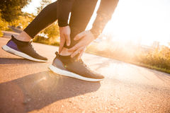 Athletic man runner touching foot in pain due to sprained ankle Royalty Free Stock Photo