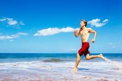Athletic Man Running on Beach Stock Photos