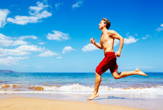 Athletic Man Running on Beach. Blue sky Royalty Free Stock Photos