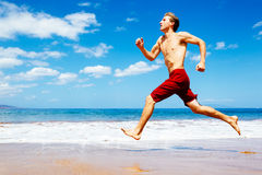 Athletic Man Running on Beach Royalty Free Stock Images