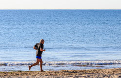 Athletic man running on  beach Stock Image