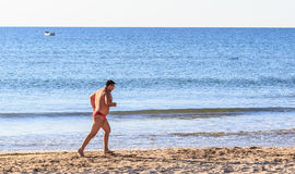 Athletic man running on  beach Royalty Free Stock Image