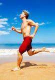Athletic Man Running on Beach Stock Photo