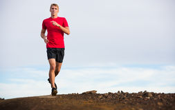 Athletic man running jogging outside, training. Athletic man jogging outside, training outdoors. Running on trail at sunset Royalty Free Stock Photo
