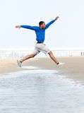 Athletic man running and jumping at beach Stock Images