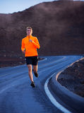 Athletic man running outside, training outdoors. Jogging on road Royalty Free Stock Images