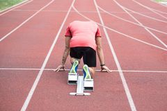 Man Runner Getting Ready to Start Sprinting Run. Athletic Man on Running Track Getting Ready to Start Run Royalty Free Stock Photo