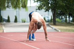 Sprinter Leaving Starting Blocks on the Running Track Stock Image