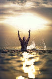 Athletic mans silhouette with raised hands out of. Athletic mans silhouette with his hands raised in the air with splash enjoying the summer sea on a beautiful Stock Image