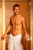 Athletic man at sauna door Stock Image