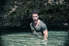 Athletic man in the sea or ocean by rocks, wet t-shirt Stock Photos