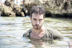 Athletic man in the sea or ocean by rocks, wet t-shirt Stock Image