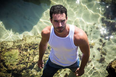 Athletic man in the sea or ocean by rocks, wet t-shirt Stock Images