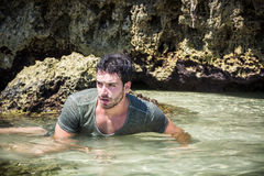 Athletic man in the sea or ocean by rocks, wet t-shirt Royalty Free Stock Photos