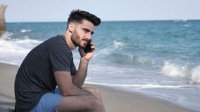 Young man by the sea talking on mobile phone. Athletic man at the seaside using cell phone to call someone with the sea behind him, sitting on a rock stock footage