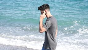 Young man by the sea talking on mobile phone. Athletic man at the seaside using cell phone to call someone with the sea behind him stock footage