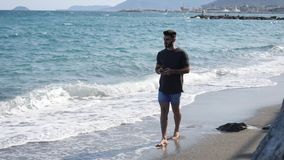Young man by the sea talking on mobile phone. Athletic man at the seaside walking, typing and then using cell phone to call someone with the sea behind him stock video footage