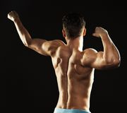 Athletic man showing his back on the black background Stock Image