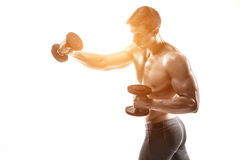 Athletic man showing muscular body and doing exercises with dumbbells Stock Photography