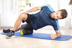 Athletic Man in Side Planking Using Foam Roller Royalty Free Stock Photos